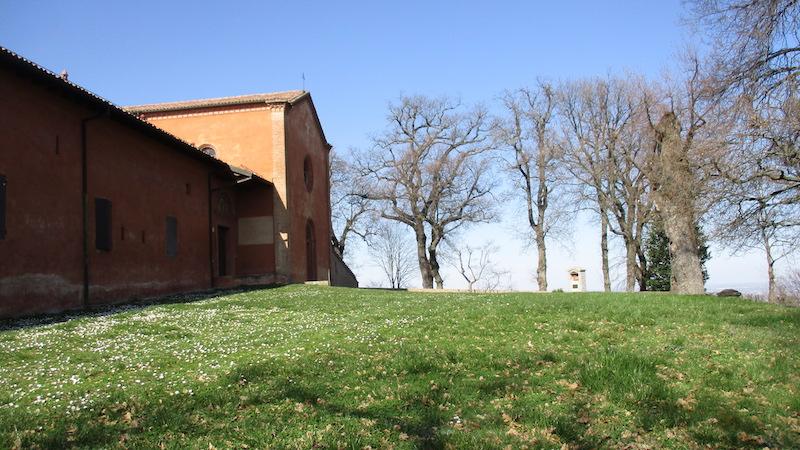 Groen gras, blauwe lucht en de oranje kerk van Eremo di Ronzano