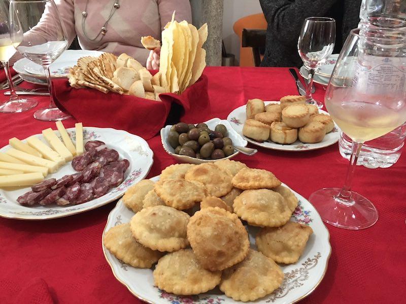 Op de voorgrond ravioli al cinghiale; daarachter pecorino e salsiccia; groene olijven; panadas; achteraan pane ladu en pane carasau