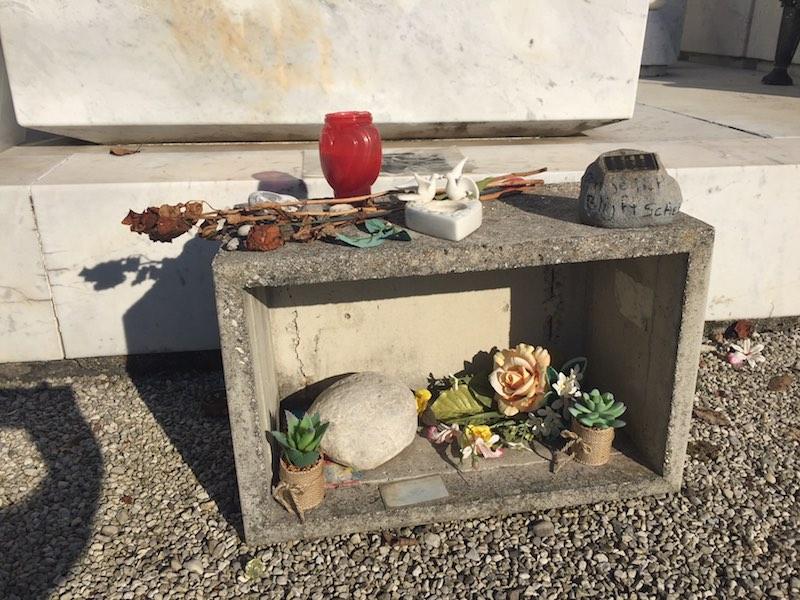 Nu liggen er wat uitgedroogde rozen, zonverkleurde plastic boeketten, een verregende foto en een gipsen madonnaatje