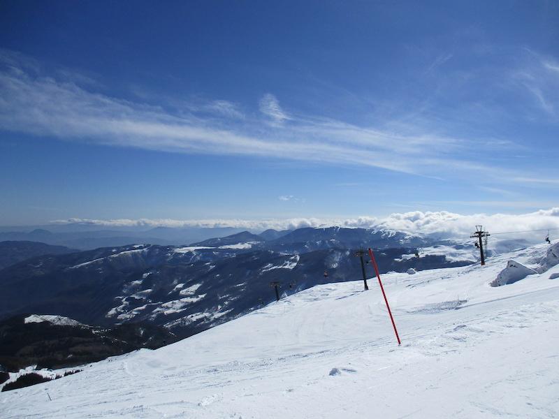 Vanaf de piste kijk je uit op de omringende heuvels en de andere pistes