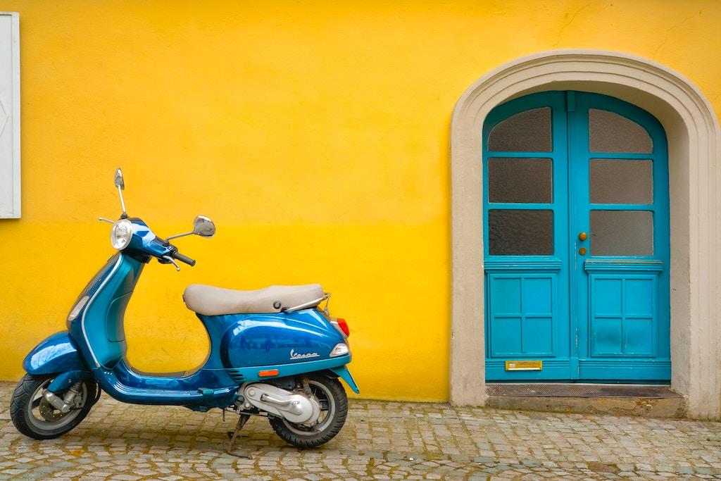 De Vespa tegen de gekleurde muur