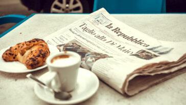 Italiaanse krant op tafel met koffie en croissant