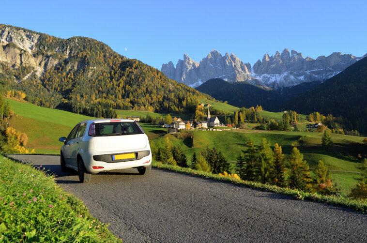 witte auto die door de Dolomieten rijdt